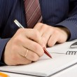 Stock Photo: Male hand writing by pen on checked notebook