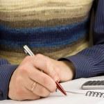 男性在笔记本上用钢笔写的手 — 图库照片