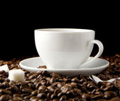 Cup of coffee and beans on black — Stock Photo