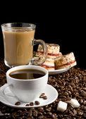 Puchar pełen ziaren kawy i ciastka na czarnym tle — Zdjęcie stockowe