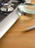 Stethoscope and keyboard with pen on wood — Стоковое фото