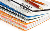Pen and pencil on checked notebook isolated on white — Stock Photo