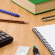Pen, pencil and paper calulator with checked notebook on wood — Stock Photo #12012866