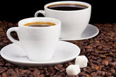 White cups of coffee on beans — Stock Photo