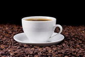 Ceramic cup of coffee and beans on black — Stock Photo
