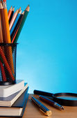 Booksa and pen with pencil in holder on blue background — Stock Photo