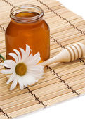 Pot of honey and flower on white — Stock Photo