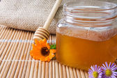 Honey in glass pot near sack — Stock Photo