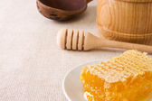 Honeycomb and pot with honey on sack — Stock Photo