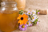 Honeycomb, flowers and honey in glass on sack — Stock Photo