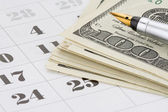 Ink pen and dollar money on calendar — Stock Photo