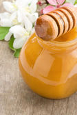 Honey in glass jar and stick — Stock Photo