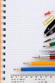 School supplies on checked notepad — Stock Photo