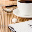 Cup of coffee, pen and pencil on notebook — Stock Photo #12112497