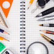 Pens, pencils, magnifying glass on cheked notebook - Stock Photo