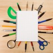 Pen, pencil and magnifier under checked notebook - Stock Photo