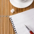 Cup of coffee and pen with notebook on table — ストック写真