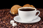 Coffee and croissant on beans — Stock Photo