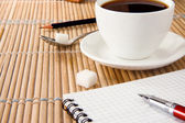 Cup of coffee, pen and pencil on notebook — Stock Photo