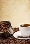Cup of coffee and pot with beans — Stock Photo