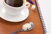 Checked notebook and coffee with pen — Stock Photo