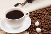 Cup of coffee, beans and grinder on sack — Stock Photo