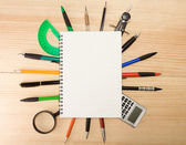 Pen, pencil and mmagnifier under checked notebook — Stock Photo