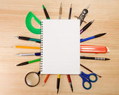 Pen, pencil and magnifier under checked notebook — Foto Stock