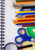 Pens, pencils, magnifying glass on notebook — Stock Photo