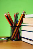 Boeken, vergrootglas en houder van de mand met potloden — Stockfoto