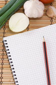 Notebook con matita, aglio, pomodoro e cipolla su trama in paglia — Foto Stock