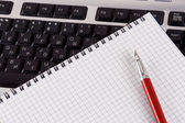 Notepad and pencil on keyboard — Stock Photo