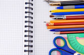 Pens, pencils and office accessories on notebook — Stockfoto
