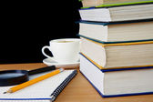 Books, pencil on notebook and cup of coffee — Stock Photo