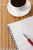 Pen on notebok and cup of coffee — Stock Photo