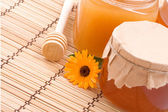 Pots of honey and flower — Stock Photo
