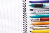 Pera, tužky a plstěnou pera na notebook — Stock fotografie