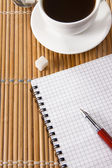 Cup of coffee and pen with notebook on table — Stock Photo
