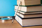 Pila de libro, lupa y tinta de pluma en madera — Foto de Stock