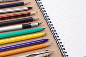 Pera, tužky a plstěnou pero poblíž poznámkového bloku — Stock fotografie