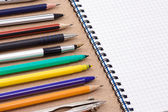Pen, pencil and felt pen near notebook — Stock Photo