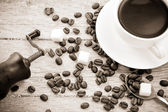 Coffee beans, grinder and cup on wood — Stock Photo