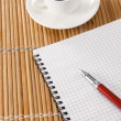 Stock Photo: Pen on notebok and cup of coffee