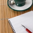 Stock Photo: Cup of coffee and ink pen with checked notebook on straw