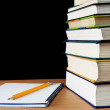 Pencil on notebook near pile of books — Stock Photo