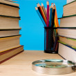 Pile of books, magnifier and holder with pencil — Stok fotoğraf