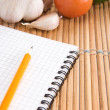 Stock Photo: Notebook, garlic and tomato with pencil in kitchen