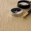 Compass, ink pen and magnifier on gold old background — Stockfoto