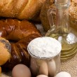 Bread, eggs, buns, flour in pot and oil on sack — Stock Photo