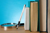 Books, magnifier and ink pen on wood — Stock Photo